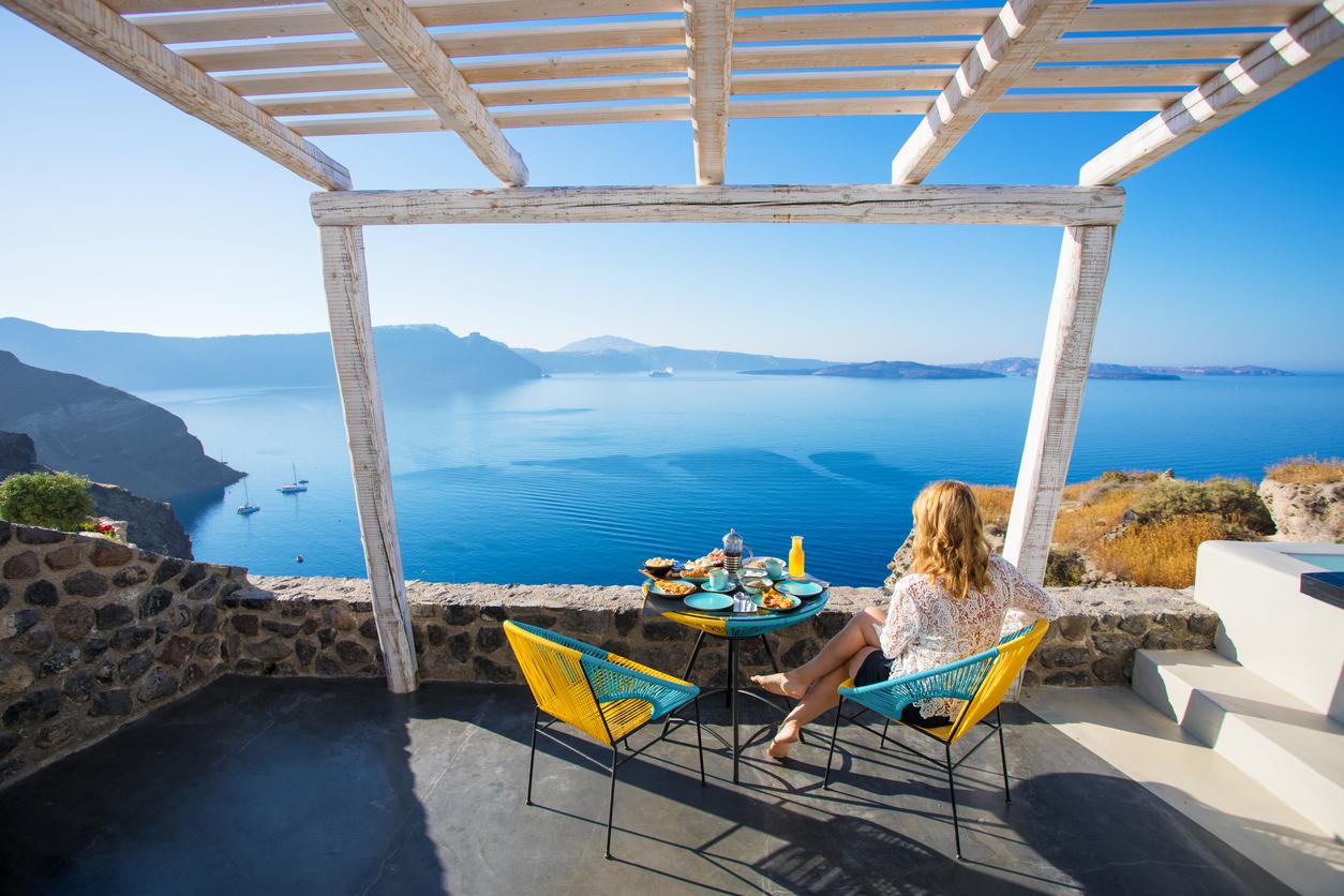 une femme prend son petit déjeuner depuis sa chambre d'hôtes vue sur Santorin