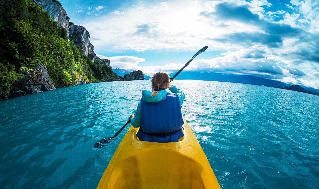 une femme fait du kayak de mer devant un paysage magnifique