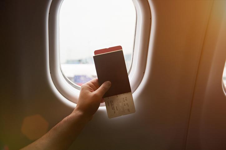 Passeport tenu devant un hublot d'avion