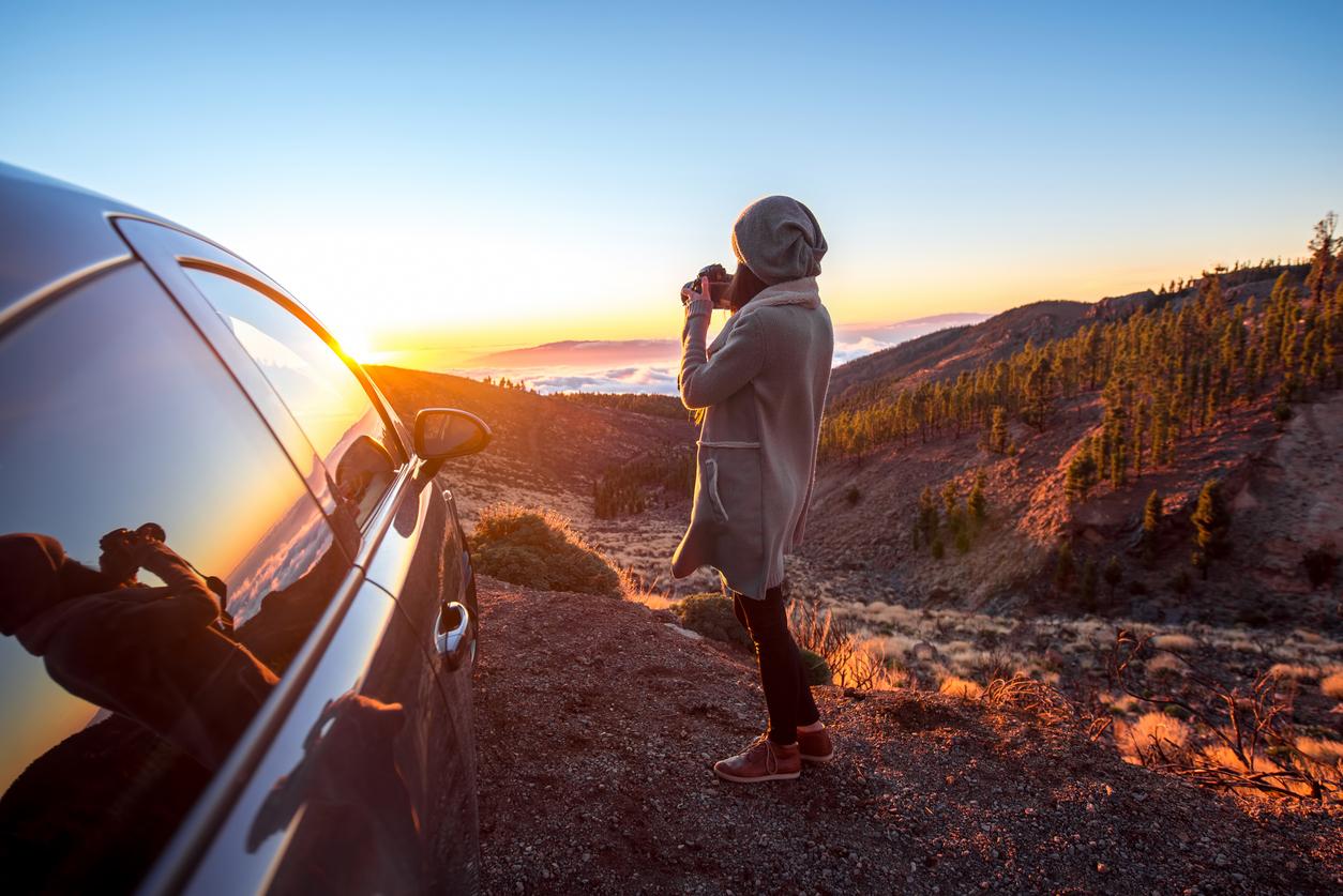 Une jeune femme s'est arrêtée sur le bord de la route pour photographier un coucher de soleil