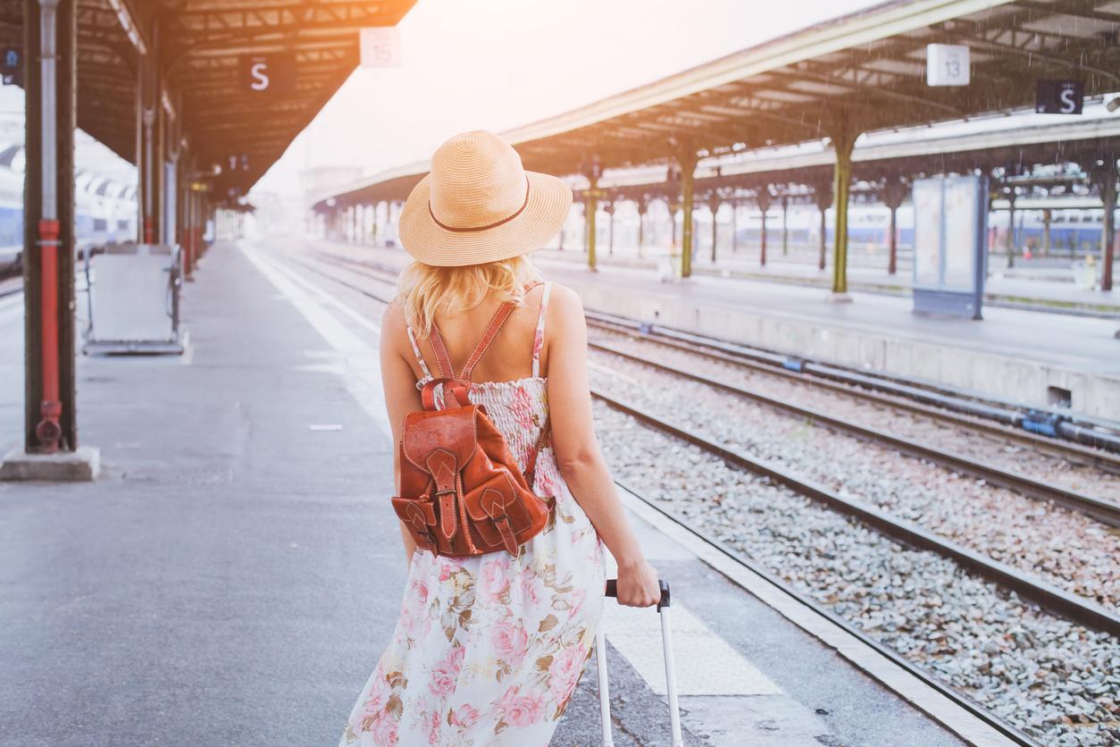 giovane donna con cappello e valigia sul binario della stazione