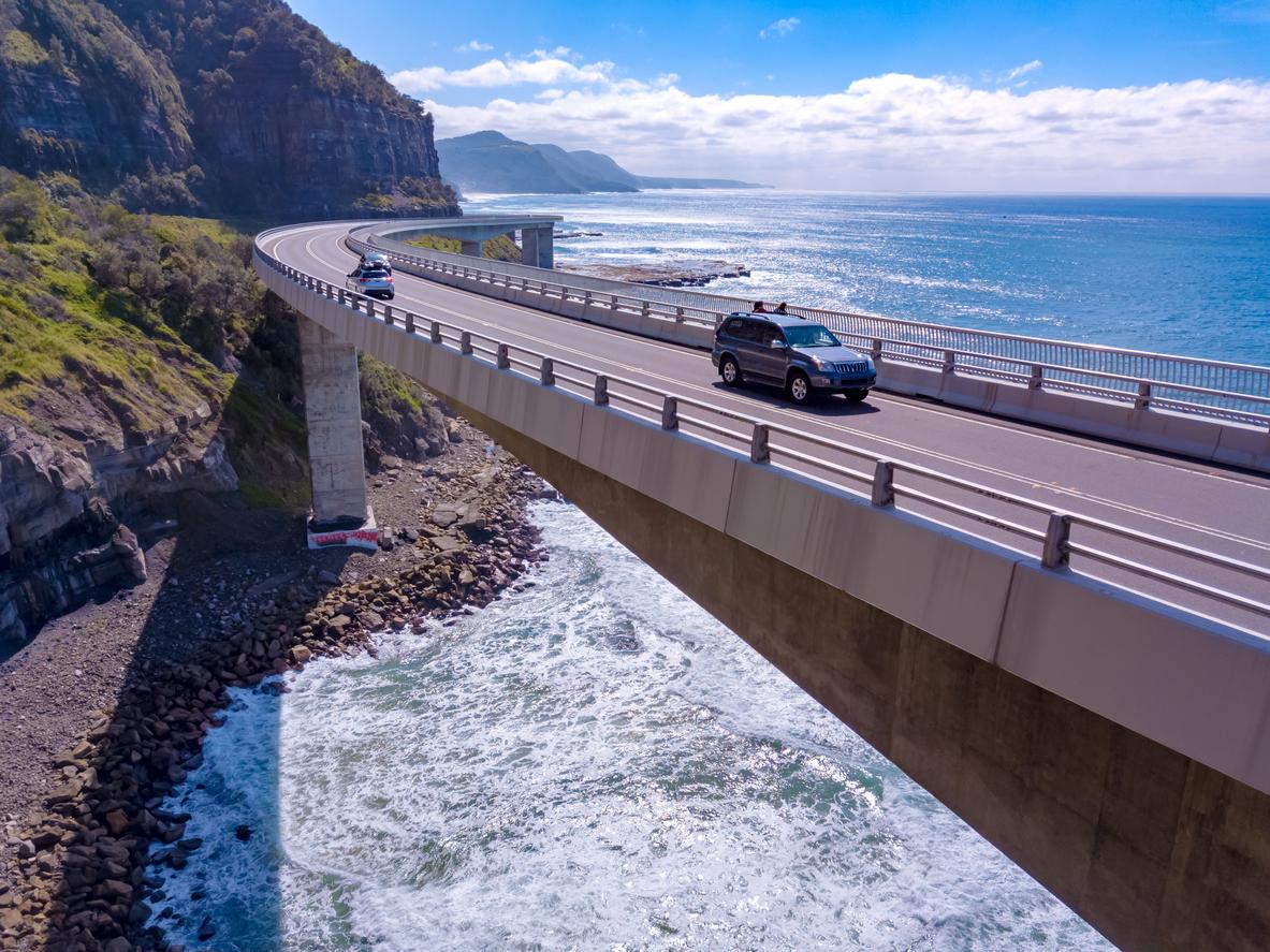 coche conduciendo en un puente sobre el mar