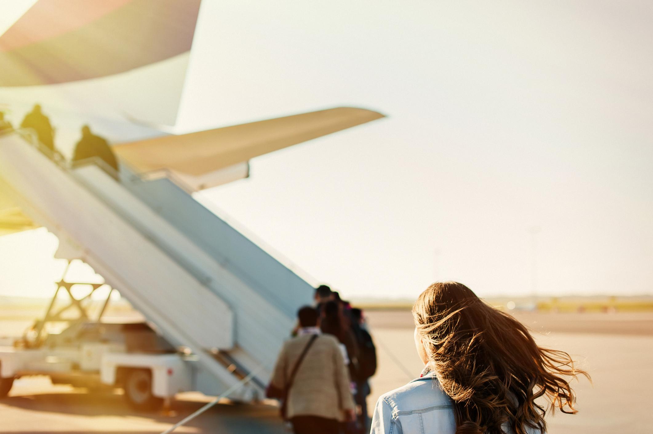 donna sull'asfalto che si imbarca su un aereo